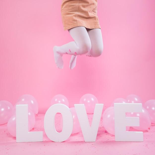 Woman jumping near love inscription Free Photo