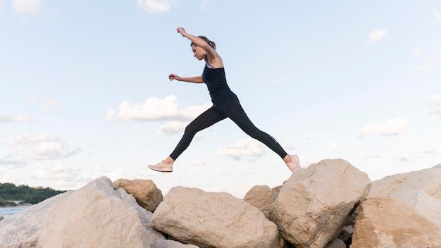La donna che salta sopra le rocce Foto Gratuite