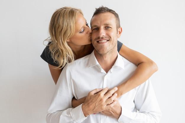 Woman kissing happy husband on cheek Free Photo