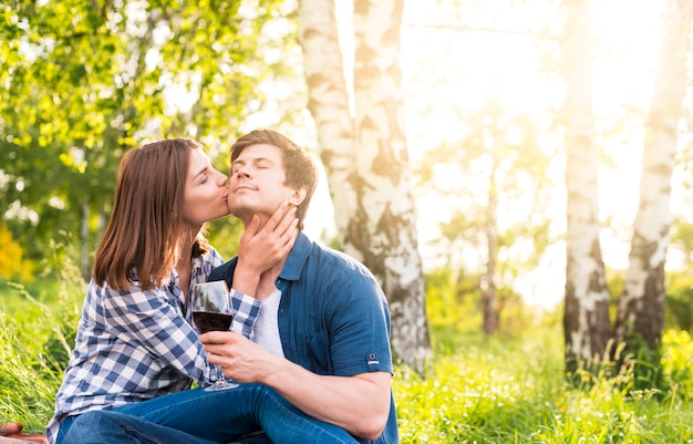 Woman kissing man on cheek amid birches Free Photo