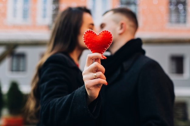 Woman kissing man while showing red heart Free Photo