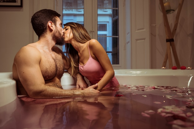 Woman kissing with young man in spa tub with water Free Photo