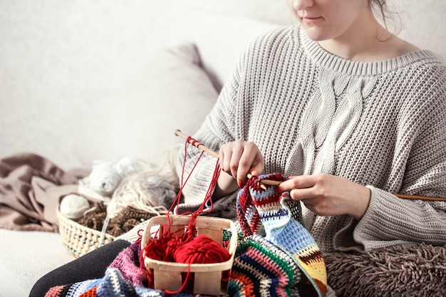 Woman knits knitting needles on the couch Free Photo