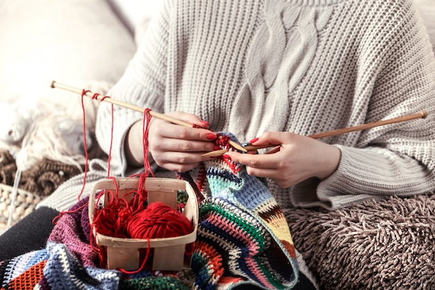女性はソファの上の編み針を編む 無料写真