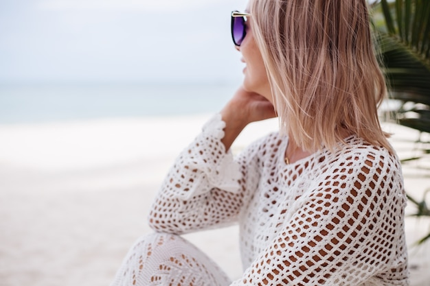 Woman in knitted white clothes on beach Free Photo