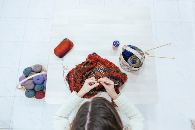 Woman knitting a woolen scarf on a white table Premium Photo