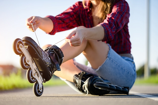 Woman laces roller skating for inline skating. teenager rollerblading outdoors. Premium Photo