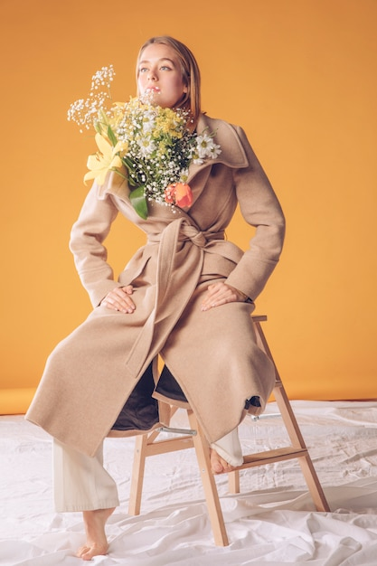 Woman on ladder with flowers bouquet in coat Free Photo