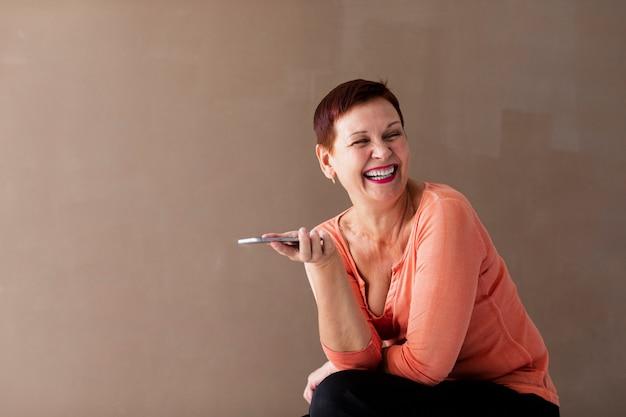 Женщина смеется и держит телефон Бесплатные Фотографии