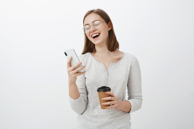 Donna che ride ad alta voce leggendo uno scherzo divertente o un meme in internet guardando lo schermo dello smartphone che tiene la tazza di caffè di carta divertendosi trascorrendo tempo divertito mentre si aspetta un amico nella caffetteria Foto Gratuite