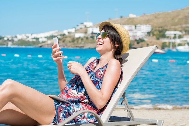 Donna che ride mentre si guarda uno smartphone Foto Gratuite
