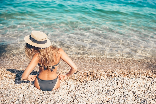 Woman laying on the beach in straw hat enjoying summer holidays looking at the sea Premium Photo