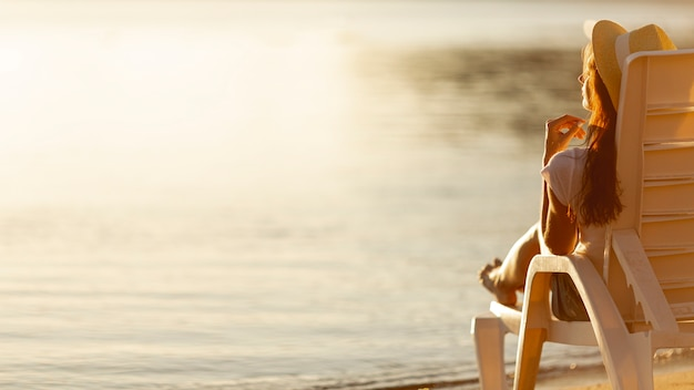 Woman laying on sunbed looking at sea Free Photo
