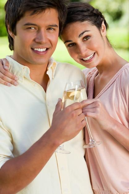 Женщина, прислонившись к другу, пока они касаются бокалов шампанского Premium Фотографии