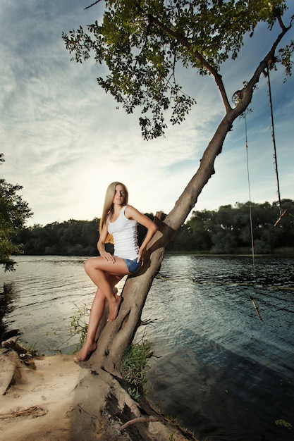 Woman leaning against a tree beside a lake Free Photo