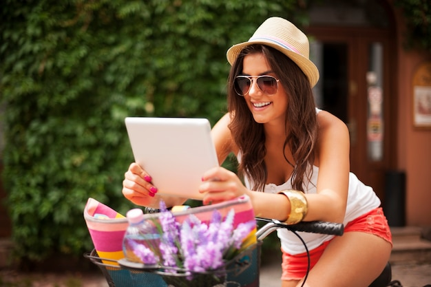 Donna che si appoggia sulla bici e controlla qualcosa sul tablet Foto Gratuite