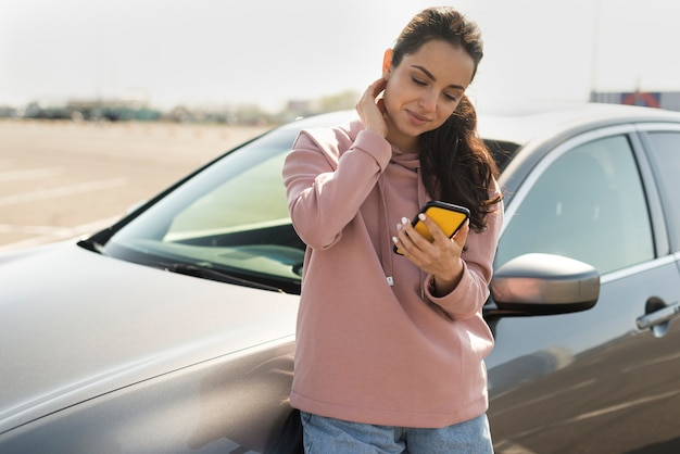 Woman leaning on the car and looking at her phone Free Photo