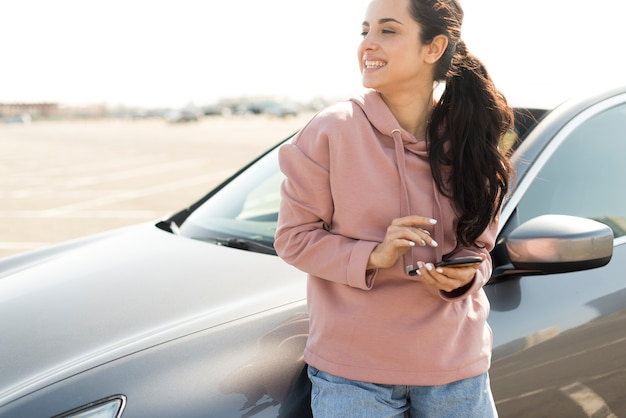 Woman leaning on the car outdoors Free Photo