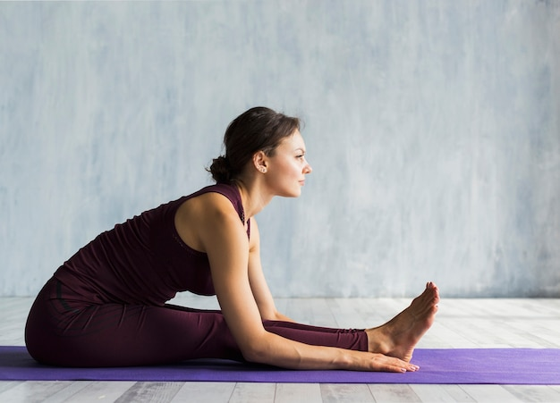 Woman leaning forward while practicing yoga Free Photo