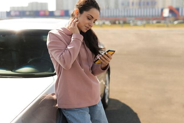 Женщина опирается на свой автомобиль Бесплатные Фотографии