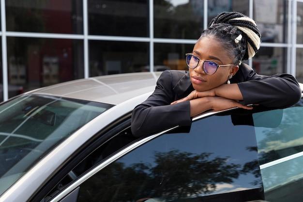 Женщина, опираясь на дверь машины Premium Фотографии