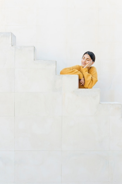 Woman leaning staircase with her eyes closed Free Photo