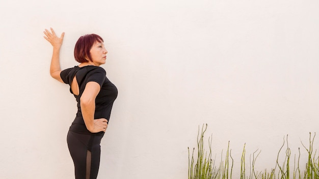 Woman leaning on a wall and stretching Free Photo