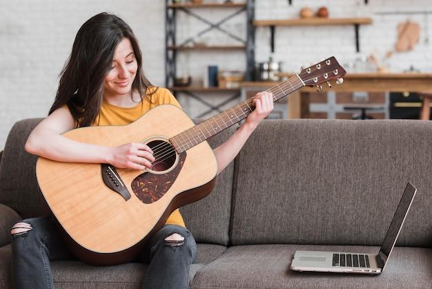 オンラインでギターの弾き方を学ぶ女性 無料写真