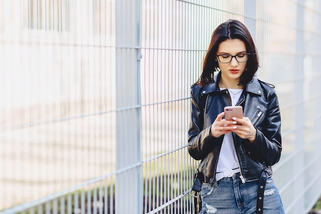 Woman in leather jacket messaging on phone at street Premium Photo