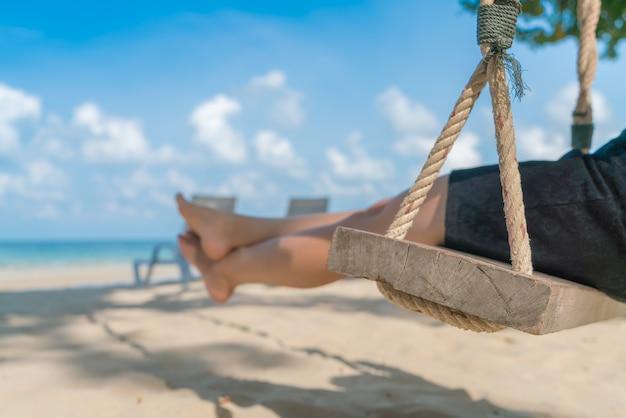 Woman leg on a swing at tropical sea beach Free Photo