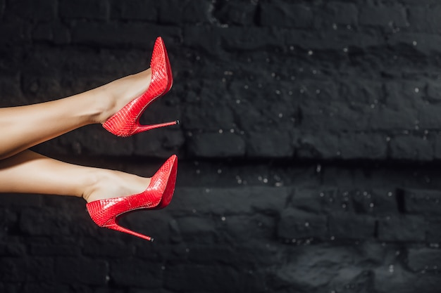 Woman legs in red shoes in the air Premium Photo