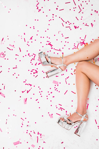 Woman legs in silver shoes at party Free Photo