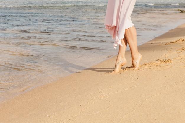 Gambe della donna che camminano sulla sabbia della spiaggia Foto Gratuite