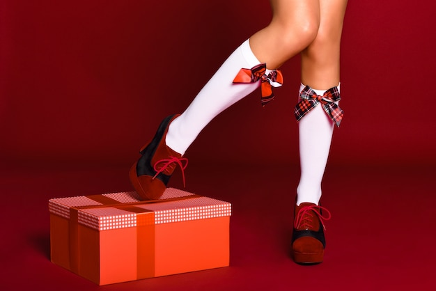 Woman legs with christmas socks with a gift box Free Photo