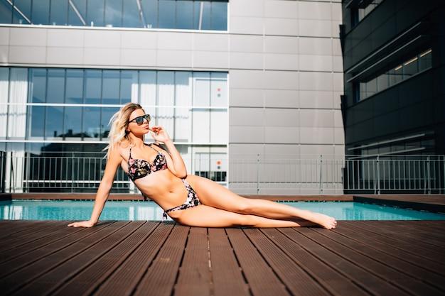 Женщина лежит на краю бассейна Бесплатные Фотографии