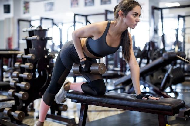 Женщина, поднимающая гантель в тренажерном зале Premium Фотографии