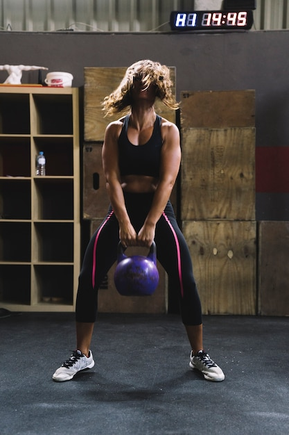 Woman lifting kettlebell Free Photo
