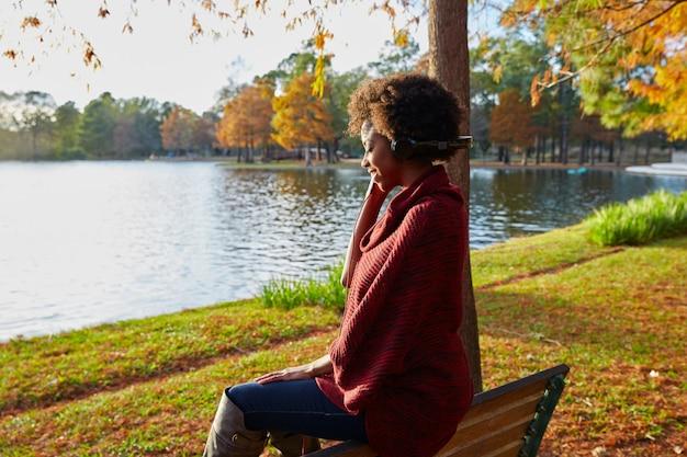 Woman listening music in the autumn park Premium Photo