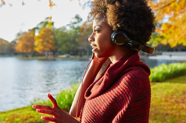 Woman listening music in the autumn park Premium Photo