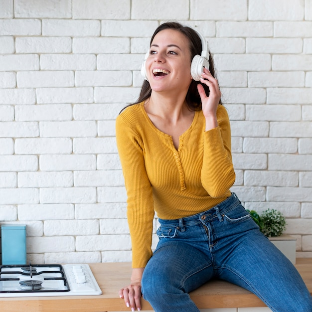 Woman listening to music and sitting on countertop Free Photo