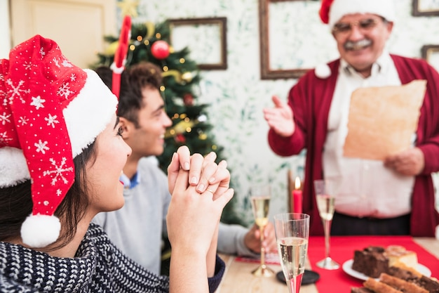 Woman listening to old man greeting at festive table Free Photo