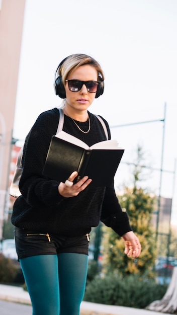 Woman listening to music and reading book Free Photo