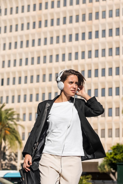 外のヘッドフォンで音楽を聴いている女性 無料写真
