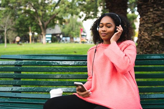 彼女の電話で音楽を聴く女性 無料写真