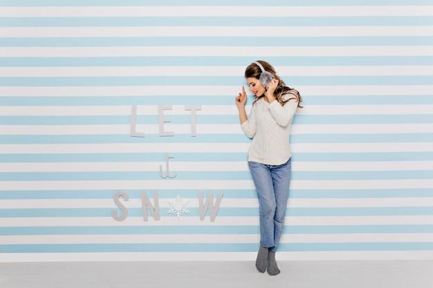 여자는 좋은 음악을 듣고 리듬을 잡으며 파란색 벽에 귀여운 옷과 재미있는 헤드폰으로 포즈를 취합니다. 무료 사진
