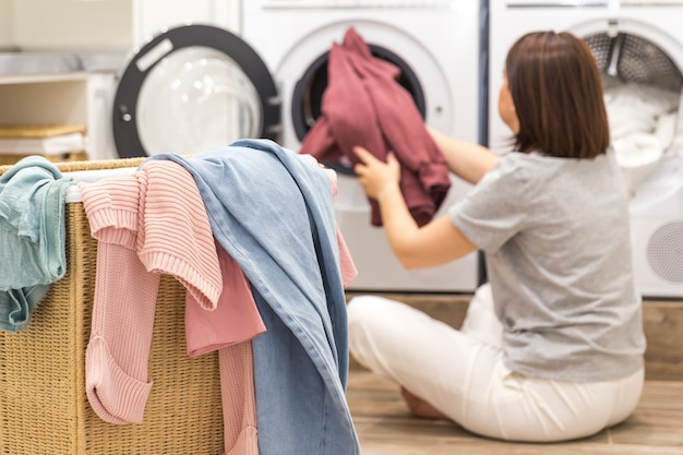 Woman loading dirty clothes in washing machine for washing in modern utility room Premium Photo