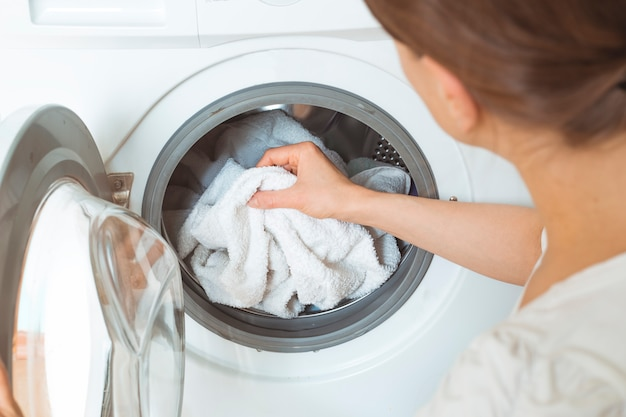 A woman loads dirty clothes for a washing machine. Premium Photo
