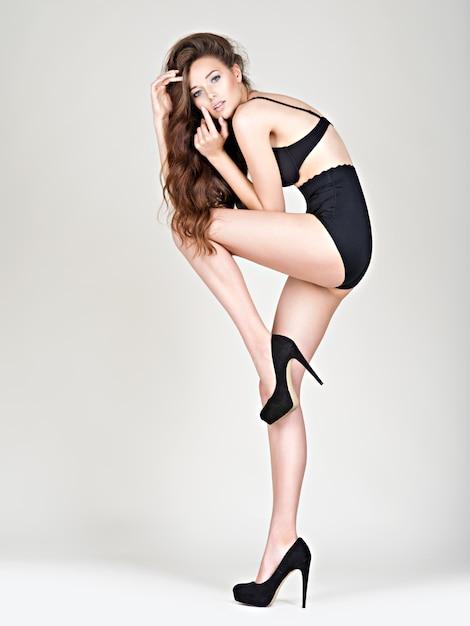 完璧なボディでハイヒールの女性の長い脚。ファションモデルがスタジオでポーズをとる黒いパンティー 無料写真