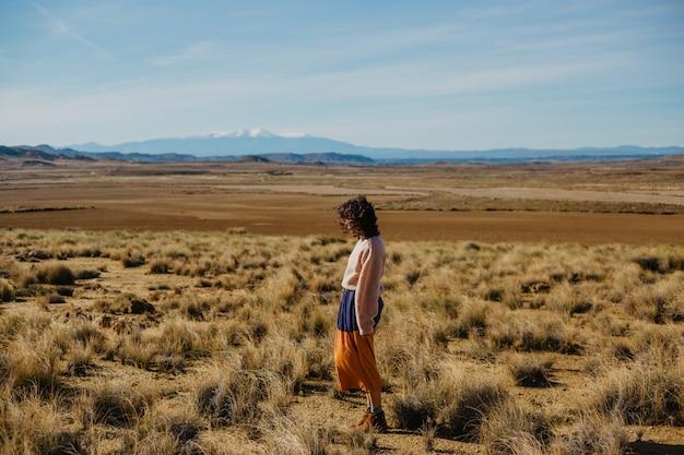 Donna in un maglione a maniche lunghe e una gonna lunga in piedi un grande brownfield con erba secca Foto Gratuite