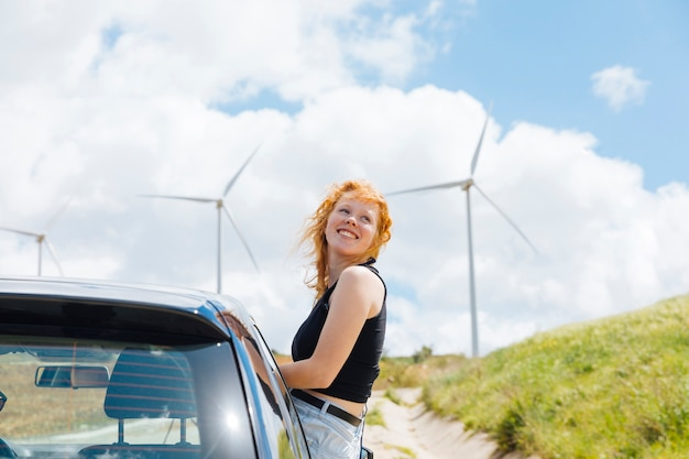 Woman looking around out of car window on sunny day Free Photo